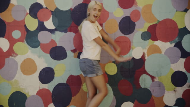 montage of carefree teenage girl dancing near dotted wall / provo, utah, united states - provo stock videos & royalty-free footage