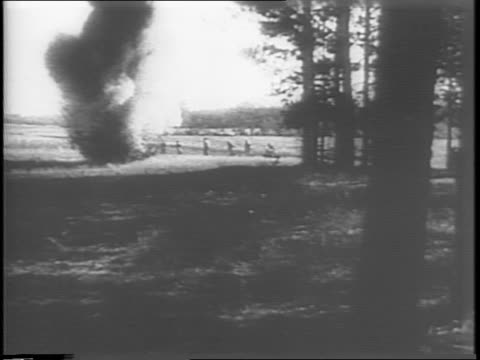 Montage of explosive rounds lighting up as they are shot explosions and smoke where they land / montage of soldiers positioning themselves behind...
