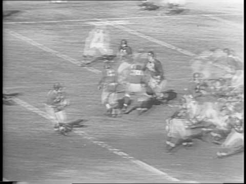 montage of game play, redskin sammy baugh fumbling and giants recovering, crowd cheering, arnie herber passing to ward cuff and scoring touchdown. - nfc east stock videos & royalty-free footage
