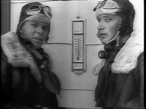 montage of high altitude pilots, 'satan's angels,' are putting on fur-lined flight clothing in locker room with electric fans / suited-up pilots pose... - us airforce stock videos & royalty-free footage