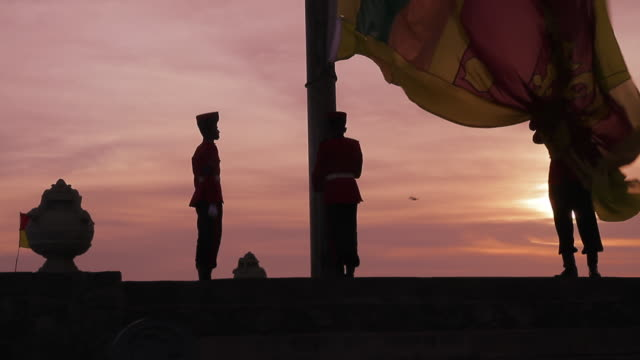 MS Montage of honour guard in full military dress lowering national Sri Lanka flag at dusk on 'Galle Face Green' / Colombo, Western Province, Sri Lanka