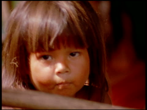 A montage of indigenous children and a mother cooking plantains on a wood fire