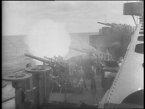Montage of line of US Navy battleship firing guns / formation of planes flying / P39 Airacobra plane firing guns / marines running up hill on beach /...