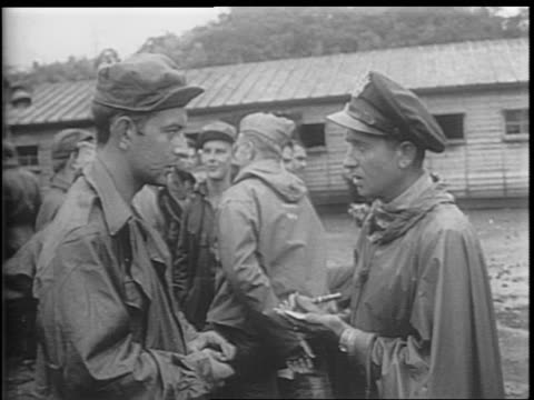 montage of living conditions at ofuna prison camp / two soldiers show a club they were beaten with / soldiers speaking to officer as officer writes... - prison camp stock videos & royalty-free footage