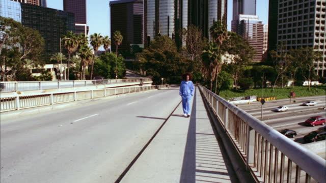 stockvideo's en b-roll-footage met ws, montage of man walking on bridge, los angeles, california, usa - waaierpalm