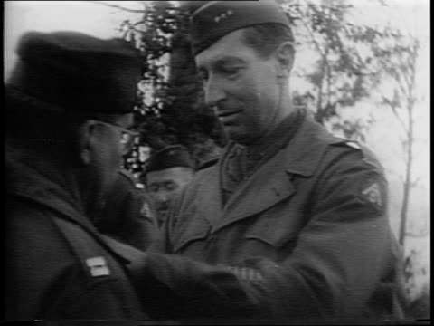 montage of mark w clark standing with lucian truscott saluting and pinning award to soldier / clark shaking hands with line of soldiers / new story /... - ピンを刺す点の映像素材/bロール
