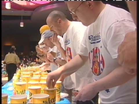 montage of men shoving hot dogs in their mouths during a eating competition. - spielkandidat stock-videos und b-roll-filmmaterial