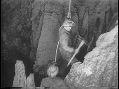 stockvideo's en b-roll-footage met montage of miners attached to ropes climbing cave wall holding pickaxes, breaking off piece of rock wall with pickax / montage of sprinklers spraying... - aan elkaar bevestigd