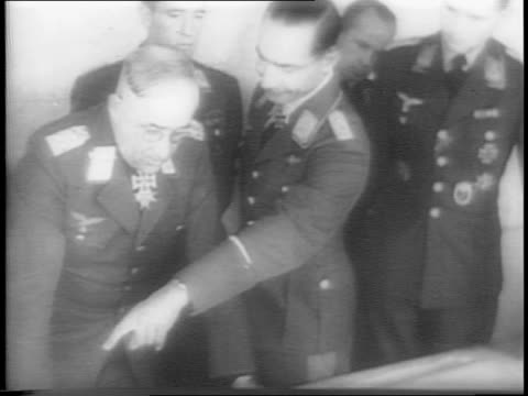 montage of nazi officers looking at a map on a table, close ups of individual officers / profile shot of heinrich himmler standing at attention in ss... - baviera video stock e b–roll