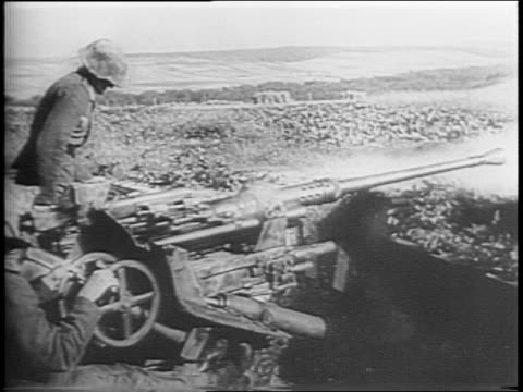 montage of nazi tanks and artillery camouflaged with greenery rolling down country roads, german soldiers consulting maps, loading and firing rounds... - 1944 stock-videos und b-roll-filmmaterial