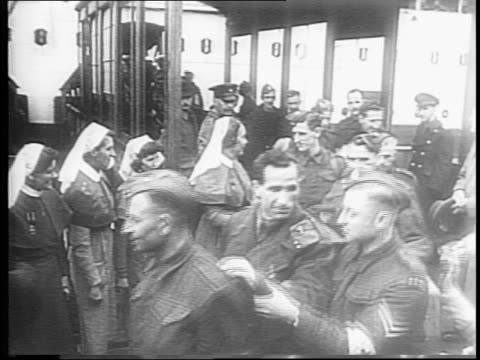 montage of nuns greeting blinded soldiers as they are led off hospital ship by fellow soldiers / soldiers with crutches walk past down off ship and... - ホームカミング点の映像素材/bロール
