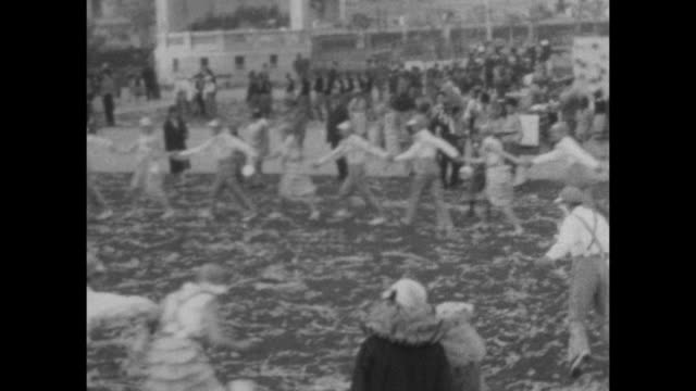 a montage of people dressed in group vintage costumes dancing in a circle wait to march at carnival in buenes aires 1927. - parade stock videos and b-roll footage
