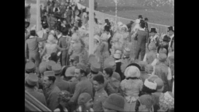 A montage of people dressed in group vintage costumes wait to march at Carnival in Buenes Aires 1927. A few groups pose for the camera.