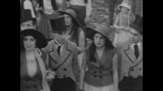 A montage of people dressed in group vintage costumes wait to march at Carnival in Buenes Aires 1927.