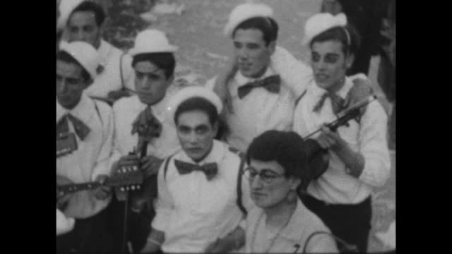 a montage of people dressed in group vintage costumes wait to march at carnival in buenes aires 1927. one man in a mask bows to the camera. - 1920 video stock e b–roll
