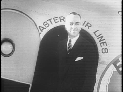 montage of pine forest in aftermath of plane crash as people inspect wreckage / captain eddie rickenbacker in doorway of eastern airlines plane /... - エディ リッケンバッカー点の映像素材/bロール