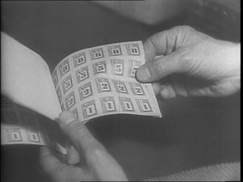 montage of ration book printing machine stamps on rollers pushing pages through cutting machine / woman worker boxes the books the boxes are hauled... - anno 1942 video stock e b–roll