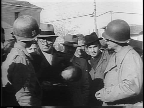 montage of refugees milling about in the streets from above, soldiers handing out cans of food, man using a stick to eat from a can, children wrapped... - anno 1944 video stock e b–roll
