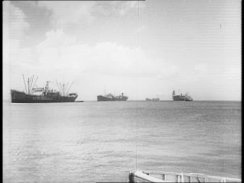 vidéos et rushes de montage of ships in martinique port, shipyards, supply yard with rows of barrels of rum under shade trees, and piles of coal / workers load barrels... - dom tom