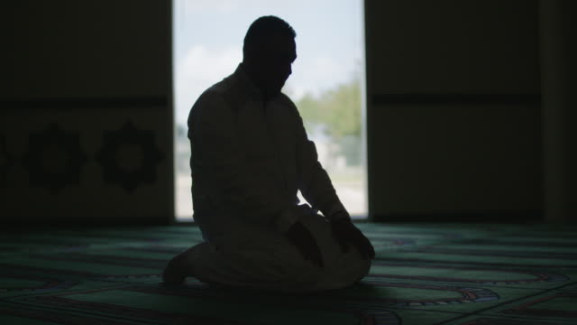 montage of silhouetted muslim man praying, slow motion - islam stock videos & royalty-free footage