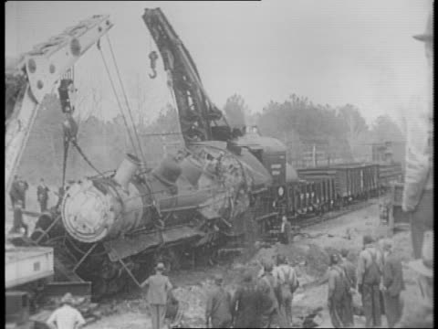 montage of smoking wreckage of train derailed railroad cars onlookers on the site / servicemen pass wreckage in new train / cranes lift engine upright - 残骸点の映像素材/bロール