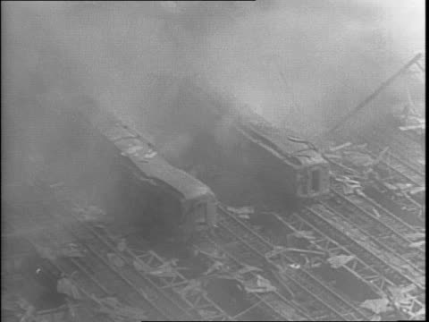 Montage of smoldering train cars on train tracks / smoke and fire damage in the train yard / montage of firefighters and onlookers on the street...