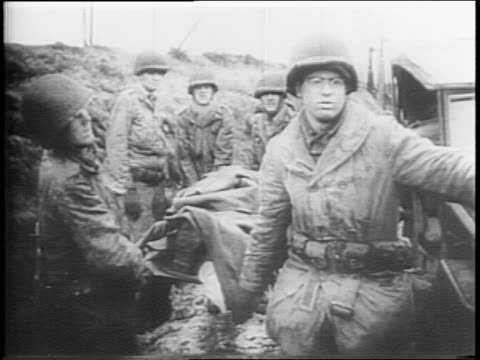 montage of soldiers advancing through forest wounded soldier aided by comrades medics dress and wrap soldier's leg wound soldiers carrying soldier on... - wrap dress stock videos and b-roll footage