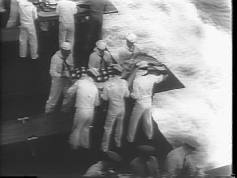 Montage of soldiers carrying stretchers with dead and wounded soldiers on battleship deck / sailors in white carry coffins to the edge of the ship...