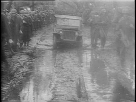 vídeos de stock e filmes b-roll de montage of soldiers marching through jungle soldiers and jeeps powering through muddy road soldier wading through muddy river view through tank... - 1944
