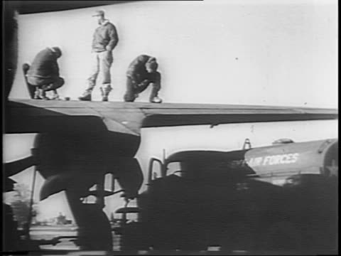 montage of soldiers next to medical truck look on as a plane crash lands military men and women looking up / bomber plane without wheels crash... - 給油点の映像素材/bロール