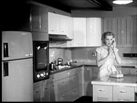 stockvideo's en b-roll-footage met montage of suburban living, woman in kitchen, man arrives home and is hugged by children. - prelinger archief