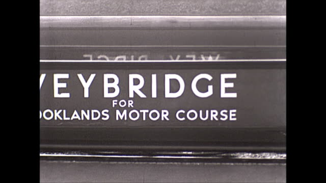 A montage of trains arriving and departing Weybridge train station in Surry UK View of Brooklands racing circuit sign / young men train spotting / CU...