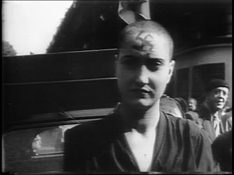 Montage of tribunal for quisling woman woman's head being shaved / female quislings with shaved heads swastikas on foreheads being led away