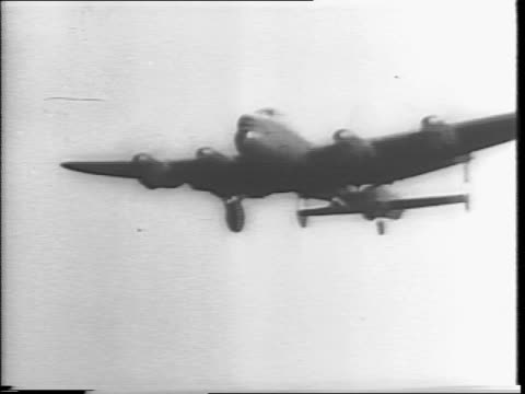 montage of truck trailer moving giant bomb backing it up to bomber plane / military crew moves bomb to be placed underneath plane / plane taking off... - lancaster bomber stock videos & royalty-free footage