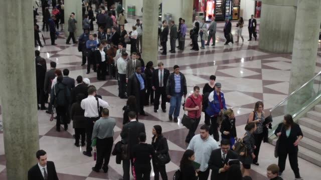 Montage of unemployed people on line waiting to get into job fair / signing up at registration table / interiors of job fair / people searching for...