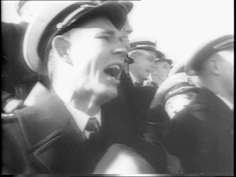 montage of uniformed navy midshipmen cheering in stands / army coach lt col earl blaik yells into a phone receiver robert jenkins pass incercepted by... - ncaa college football stock videos and b-roll footage