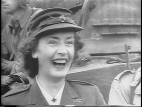 vidéos et rushes de montage of women in uniform, civilians smiling and waving / women in crowd looking at camera / montage of aerials of american troops marching in... - 1944