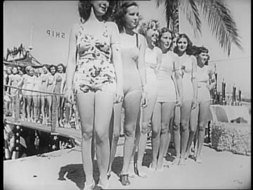 montage of women's legs / crowd of women at department store counter behind which are saleswomen with silk stockings / government executive harriet... - 絹点の映像素材/bロール