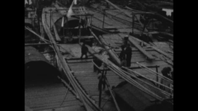 vidéos et rushes de a montage of work scenes at the bund (waterfront area) on the huanpu river. men sail on junks on the river. - jonque