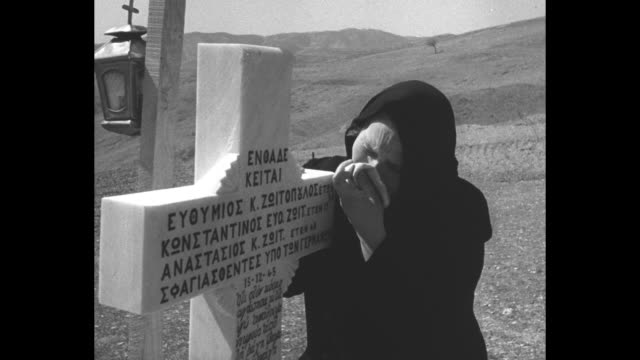 vidéos et rushes de montage old woman stands in cemetery in greek village of kalavryta, weeps at stone cross monument bearing elaborate inscription; the village has been... - guerre civile