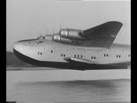montage pan american airways system seaplane glides on water, takes off / black / end credits / from greatest headlines of the century series / note:... - 航空便点の映像素材/bロール