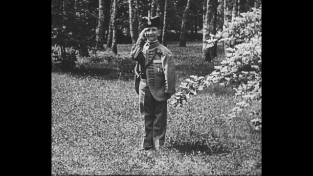 montage peter ii, young son of slain king alexander i of yugoslavia, wears military uniform as he salutes while outdoors / note: exact month/day not... - mord stock-videos und b-roll-filmmaterial