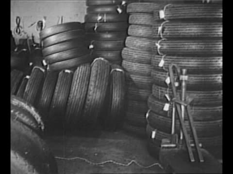 vídeos de stock e filmes b-roll de montage piles of automobile tires with tags at goodrich tire plant in long island city, ny, in 1942 / artillery guns on trailers pass by camera, with... - carroça puxada por cavalo