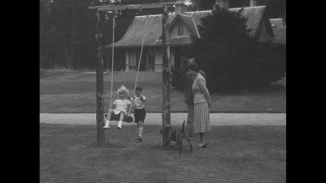 montage prince charles pushes princess anne on swing on grounds of balmoral castle as philip, duke of edinburgh, looks on / montage duke pushes both... - queen royal person stock videos & royalty-free footage