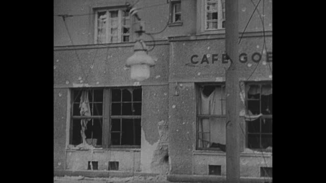 Montage quick shots representing types of news from 1934 including soldiers with artillery bullet holes in EXT Austrian cafe crowd running away...