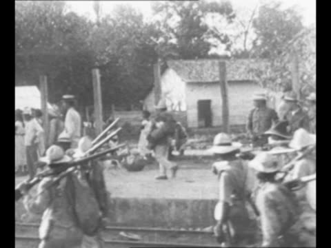 montage rebel troops walk in nicaragua / nicaraguan rebels aim rifles off side of boat / montage rebels on boat with rifles cannon / from greatest... - 中央アメリカ点の映像素材/bロール
