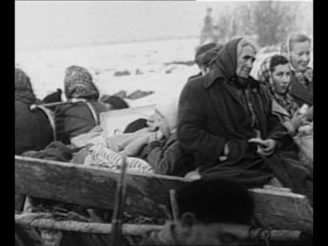 stockvideo's en b-roll-footage met montage refugees ride on cart / woman comforts small child in her arms / black / end credits / from greatest headlines of the century series - 1956