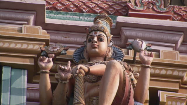 A montage reveals three statues on a temple including a statue with four arms. Available in HD.
