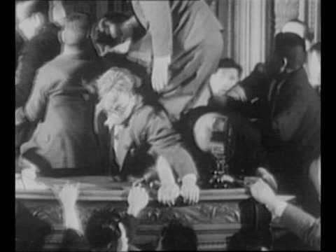 Montage riot in the Japanese Diet with several members trying to remove a grayhaired Socialist with eyeglasses who is hanging on to the speaker's...