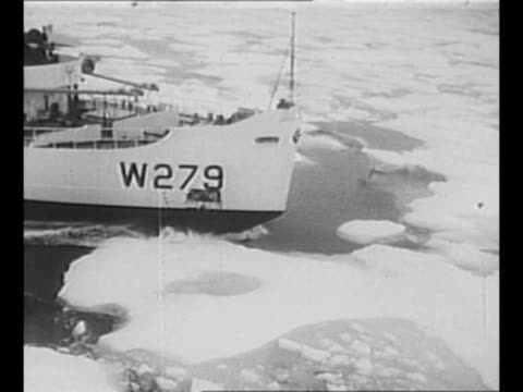 montage ship moves through ice in water / crew member stands on wet deck bundled up and looks over rail / ls ship in water with ice chunks mountains... - landungsboot stock-videos und b-roll-filmmaterial